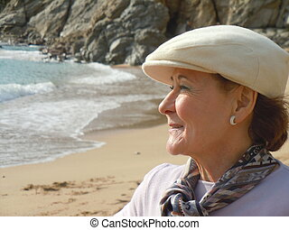 senior woman looking at the sea - smiling senior woman...