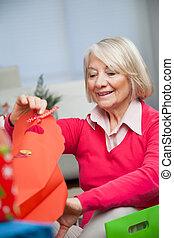 Smiling Senior Woman Looking In Bag At Home