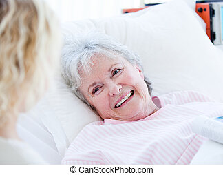 Smiling senior woman lying on a hospital bed talking with her granddaughter. Medical concept.