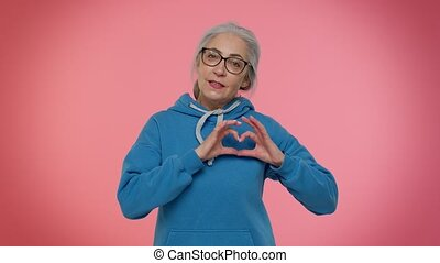Smiling elderly granny gray-haired woman in makes heart gesture demonstrates love sign expresses good feelings and sympathy. Senior old grandmother on pink background. People lifestyle emotions