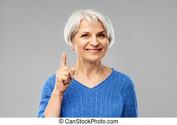 smiling senior woman pointing finger up