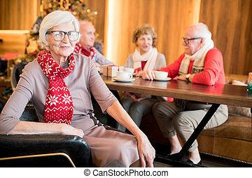 Smiling senior woman resting with friends in coffee shop