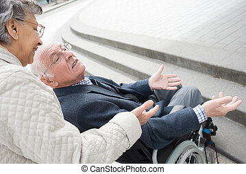 smiling senior woman talking to her husband in a wheelchair