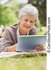 Smiling senior woman using digital tablet at park