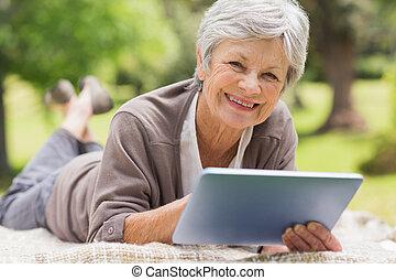 Smiling senior woman using digital