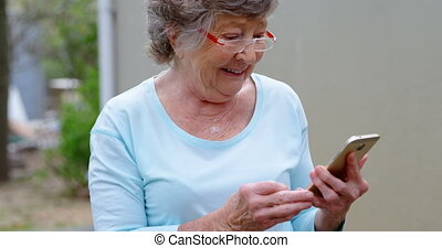 Senior woman using mobile phone 4k - Smiling Senior woman...