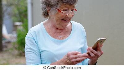 Senior woman using mobile phone 4k - Smiling Senior woman...
