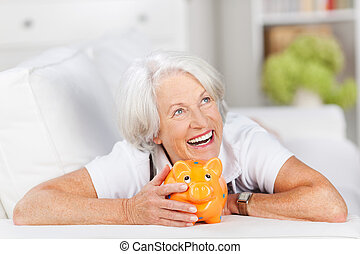 Smiling senior woman with a piggy bank