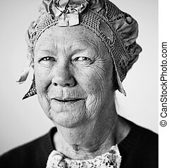Senior smiling woman in the studio wearing a vintage hat and lace.