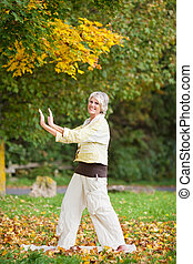 Smiling Senior Woman With Arms Raised Doing Yoga