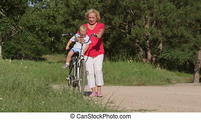 Smiling senior woman with grandson enjoying time together on bicycle