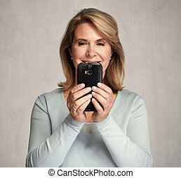 Smiling senior woman with smartphone