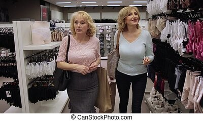 Smiling senior women shopping at clothing store - Smiling...
