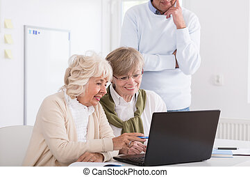 Smiling senior women looking at laptop's screen