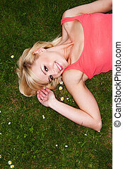 Smiling sexy blonde relaxing on grass