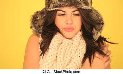 Smiling Sexy Woman In Winter Outfit on yellow studio background