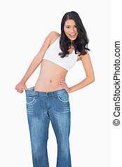 Smiling sexy woman wearing too big jeans
