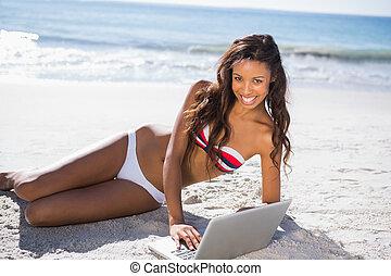 Smiling sexy young woman in bikini using her laptop