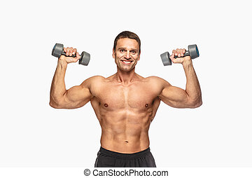 Smiling shirtless male with dumbbells.