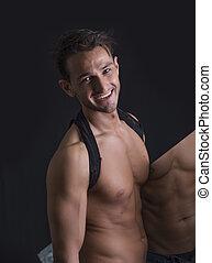 Smiling shirtless man holding mirror