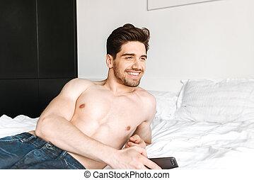 Smiling shirtless man holding mobile phone