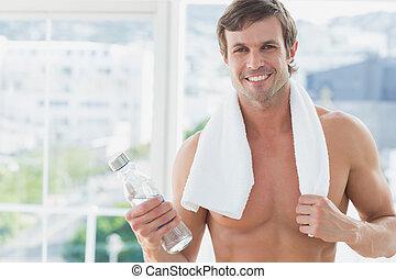 Smiling shirtless man holding water bottle in fitness studio