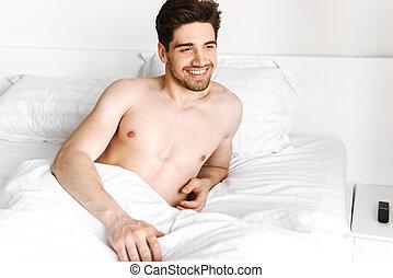 Smiling shirtless man laying in bed
