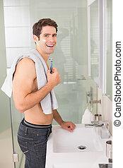Smiling shirtless man shaving in bathroom