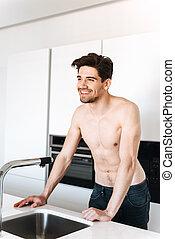 Smiling shirtless man standing at the kitchen