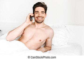 Smiling shirtless man talking on mobile phone