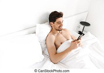 Smiling shirtless man using mobile phone