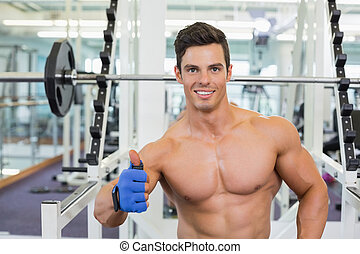 Smiling shirtless muscular man giving thumbs up in gym - ...