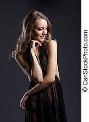 Smiling shy woman posing in black erotic negligee