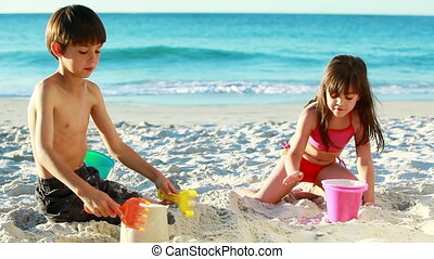 Smiling siblings building sand castles on the beach