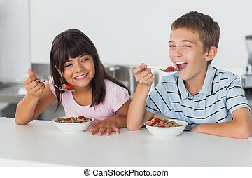 Smiling siblings eating cereal for breakfast in kitchen