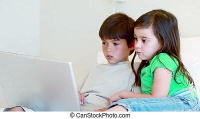 Smiling siblings looking at a laptop