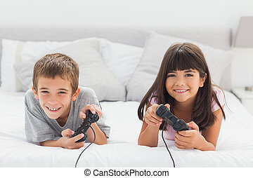 Smiling siblings lying on bed playing video games together...