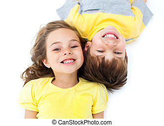 Smiling siblings lying on the floor against a white ...