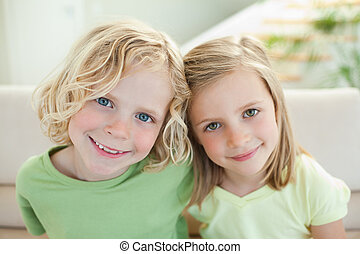 Smiling siblings on the sofa