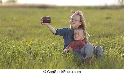 Smiling siblings taking selfie in the meadow