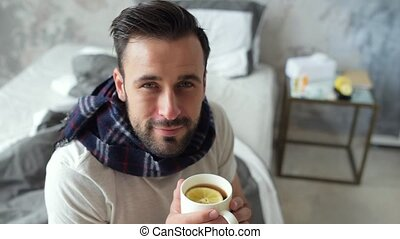Smiling sick guy looking into camera while drinking tea