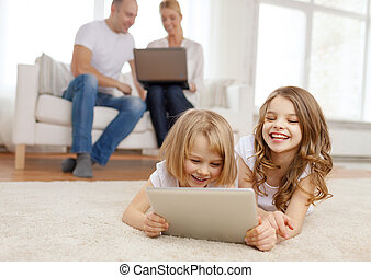 smiling sister with tablet pc and parents on back