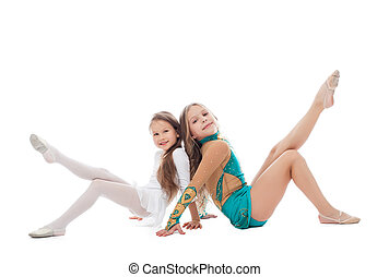 Smiling sisters gymnasts isolated on white background