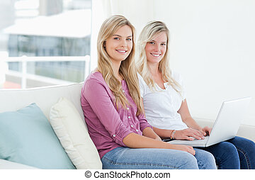 Smiling sisters sit on the couch holding a laptop while they look to the side into the camera