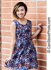 Smiling Slender Asian American Woman Standing In Dress