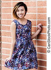 Smiling Slender Asian American Woman Standing In Dress