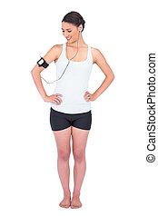 Smiling slender model wearing armband holding mp3 player