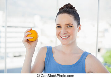 Smiling slender woman in sportswear holding orange