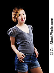 Smiling Slim Asian American Woman In Jean Shorts And Sweater