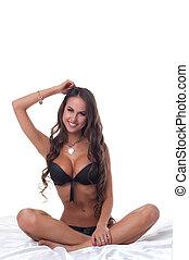 Smiling slim girl posing sitting on bed in studio